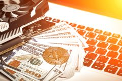 Bitcoins with dollar bills on laptop keyboard. Bitcoin. New virtual money. Video card, concept of mining. Sun flare Royalty Free Stock Images