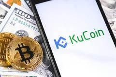 Bitcoins, dollars avec le logo de KuCoin sur le smartphone d'?cran images stock