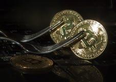 Bitcoins dorati con le forcelle Concetto duro del cambiamento della forcella Fotografia Stock Libera da Diritti