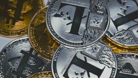 Bitcoins dorati e d'argento e litecoins che girano sulle fatture di 100 dollari archivi video
