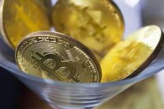 Bitcoins dorati in un primo piano di vetro di cocktail Immagini Stock