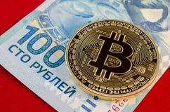 Bitcoins dorato (soldi virtuali digitali) e cento rubli Fotografie Stock Libere da Diritti