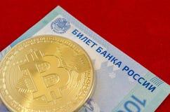 Bitcoins dorato (soldi virtuali digitali) e cento rubli Fotografia Stock Libera da Diritti