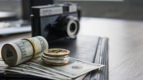 Bitcoins dourados em uma parte superior de outras moedas e no conta dos dólares americanos com uma câmera da foto em um backgroun Fotos de Stock