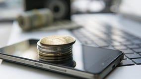 Bitcoins dourados em uma parte superior de outras moedas e no telefone esperto e em um portátil Currebcy cripto de Bitcoin Digita Imagem de Stock