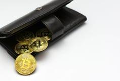 Bitcoins dourados na carteira preta, símbolo de Digitas de uma moeda virtual nova com fundo branco Foto de Stock
