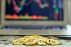 Bitcoins e banconote in dollari dell'oro che compaiono da sopra un computer portatile con i grafici di borsa valori sullo schermo immagine stock