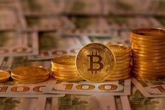 Bitcoins empilhou em notas de dólar novas do projeto 100 Fotografia de Stock Royalty Free