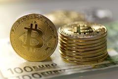 Bitcoins en cientos billetes de banco del euro Foto de archivo libre de regalías