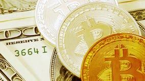Bitcoins en dollarsclose-up De muntstukken van bitcoin van gouden kleur liggen op honderd-dollar rekeningen De schuif van de moti stock video