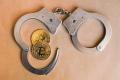 Bitcoins en handcuffs als een abstract symbool van misdaad dat h kan stock fotografie