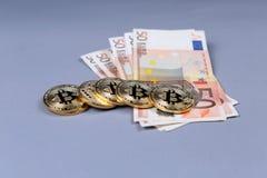 Bitcoins and Euro banknotes Stock Photos