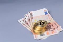Bitcoins and Euro banknotes Stock Image
