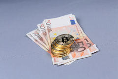 Bitcoins and Euro banknotes Royalty Free Stock Photo