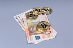 Bitcoins and Euro banknotes Royalty Free Stock Image