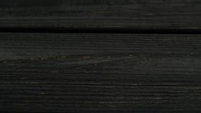 Bitcoins fall on the dark boards. Close up. Bitcoins shiny fall to shabby dark wenge boards. Close up stock video