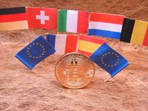 Bitcoins and a few European flags. Germany , Switzerland, Italy, Luxembourg, Belgium, European Union, France and Spain on golden background stock images