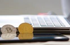 Bitcoins fisici che si appoggiano computer portatile Fotografia Stock