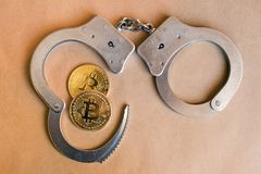 Bitcoins and handcuffs as an abstract symbol of crime that can h stock photography