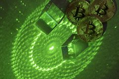 Bitcoins and hexagons, prisms and laser light. Bitcoins on grainy concrete table with green laser light