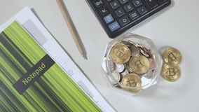 Bitcoins inside a jar with savings. Close-up. Camera moves from up to down. Bitcoins are in the glass jar with savings. The calculator, pencil and notepad are stock footage