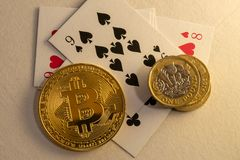 Bitcoins laying down on the table with bunch of coins and cards in the background. Online gambling concepts stock image