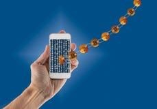 Bitcoins liés laissant le smartphone tenu dans la main Photos libres de droits