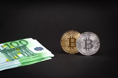 Bitcoins lie on a dark background with euro, close-up royalty free stock image