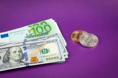 Bitcoins ligt op een purpere achtergrond met dollars en euro close-up stock afbeelding