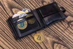 Bitcoins, litecoin и ethereum в черном кожаном бумажнике на деревянной предпосылке Стоковая Фотография