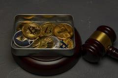 Bitcoins, litecoin en ethereum liggen in metaaldoos op oude houten achtergrond met rechtershamer stock afbeelding