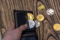 Bitcoins, litecoin and ethereum in black leather wallet in man hand on wooden background. Closeup Stock Image