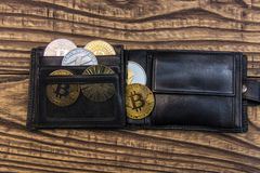 Bitcoins, litecoin and ethereum in black leather wallet on wooden background. Closeup Stock Image