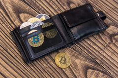 Bitcoins, litecoin and ethereum in black leather wallet on wooden background. Closeup Stock Photography