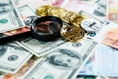 Bitcoins through magnifying glass on the real money background. Investment, risk, business stock image