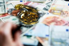 Bitcoins through magnifying glass on the real money background. Investment, risk, business royalty free stock image