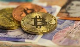 Bitcoins med brittiska sedlar, 20 pund ett pund sterling, 10 pund anmärkningar guld- bitcoin, silverbitcoin, brons Arkivbilder