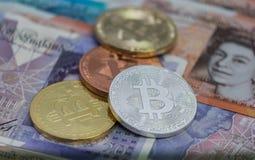Bitcoins med USA-sedlar och brittiska sedlar, 20 pund ett pund sterling, 10 pund anmärkningar guld- bitcoin, silver Arkivfoton