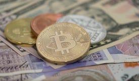 Bitcoins met de bankbiljetten van de V.S. en Britse bankbiljetten, 20 pond Sterling, 10 pond Sterlingnota's gouden bitcoin, zilve Stock Foto's