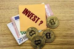 Bitcoins, moneda del pedazo en el euro, dólares observa la nota pegajosa de la bruja sobre fondo de madera, `` INVIERTE `` Fotos de archivo