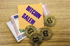 Bitcoins, moneda del pedazo en el euro, dólares observa la nota pegajosa de la bruja sobre el fondo de madera, VENTA de BITCOIN Foto de archivo libre de regalías