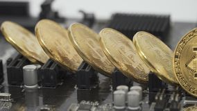 Bitcoins on motherboard. Close-up. Bitcoins on motherboard. Five coins stands on the edge. Camera moves from left to right. It stops, focus on the bitcoin stock video