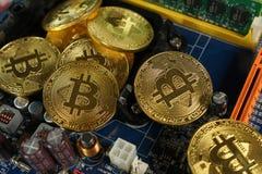 Bitcoins na płycie głównej Crypto waluta Złocisty Bitcoin kawałek moneta - BTC - Zdjęcie Stock