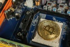 Bitcoins na płycie głównej Crypto waluta Złocisty Bitcoin kawałek moneta - BTC - Zdjęcia Royalty Free