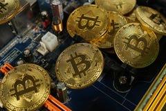 Bitcoins na płycie głównej Crypto waluta Złocisty Bitcoin kawałek moneta - BTC - Zdjęcia Stock