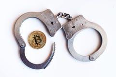 Bitcoins och handbojor som ett abstrakt symbol av brottet som kan H Royaltyfria Foton