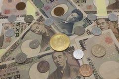 Bitcoins och japanska pengar royaltyfri foto