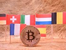 Bitcoins och några europeiska flaggor Arkivbild