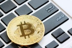 bitcoins placed on a black keyboard to see enter button in Crypt stock image