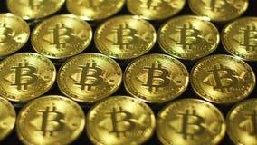 Bitcoins que brillan tenuemente de oro en el arreglo almacen de metraje de vídeo
